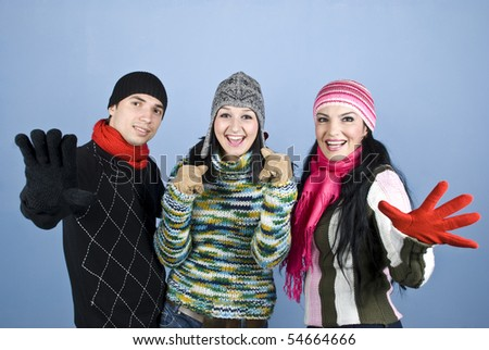 Happy smiling three friends showing happiness and excitement and standing with hands gloves in front of image over blue background