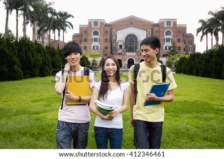 Happy smiling three  standing together with books at a campus - stock photo