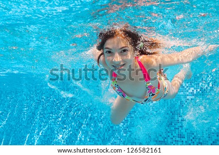 Happy smiling underwater child in swimming pool, beautiful healthy girl swims and having fun in water. Kids sport on family summer vacation. Active holiday - stock photo