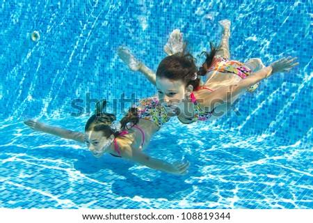 happy smiling underwater children in swimming pool beautiful girls swim and having fun kids - Kids Swimming Underwater