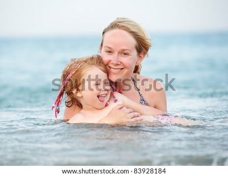 Happy smiling Woman and child playing in red sea water - stock photo