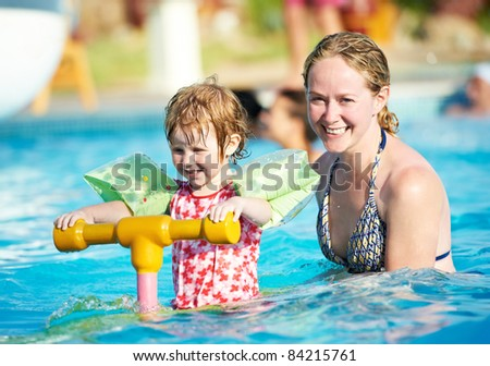 Happy smiling Woman and child playing in swimming pool - stock photo