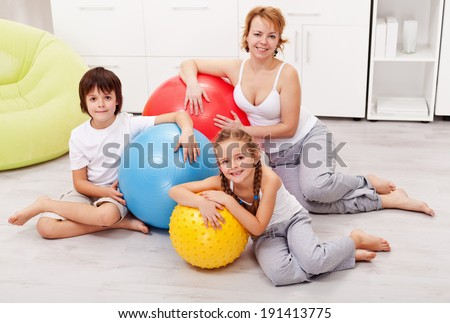 Happy smiling woman and kids exercising at home using large gymnastic walls - stock photo