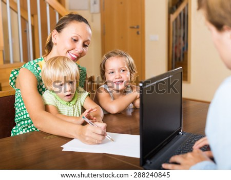Happy smiling woman and two little daughters sitting in front of social worker  - stock photo