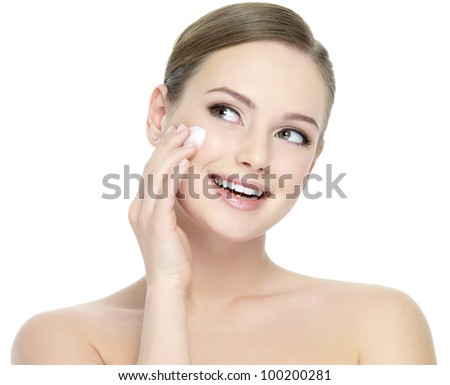 Happy smiling woman applying cosmetic moisturizer cream - isolated on white - stock photo