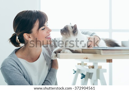 Happy smiling woman at home cuddling and holding her lovely cat on a table, pets and togetherness concept - stock photo