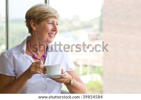 happy smiling woman drinking coffee by the window - stock photo