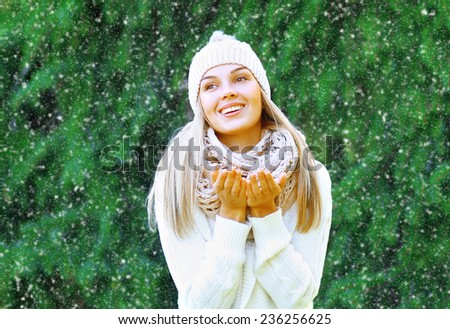 Happy smiling woman having fun outdoors and enjoys the snow - stock photo