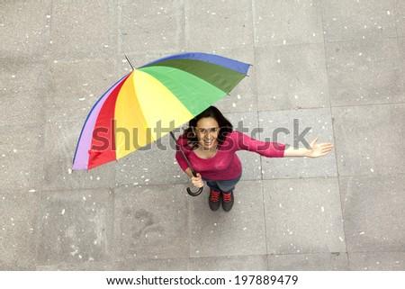 Happy smiling woman hidden under multicolored umbrella  - stock photo