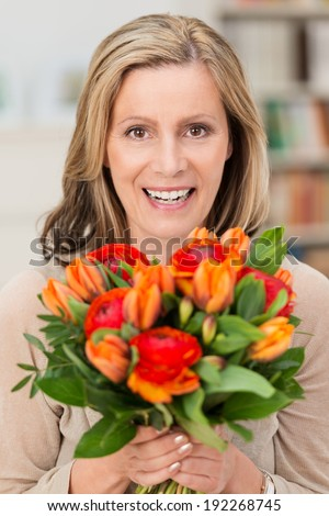 Happy smiling woman holding a gift of fresh orange flowers in a large bouquet on her birthday, Mothers Day, anniversary or Valentines - stock photo