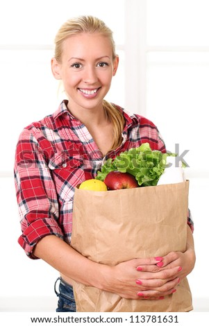 Happy smiling woman holding a grocery bag - stock photo