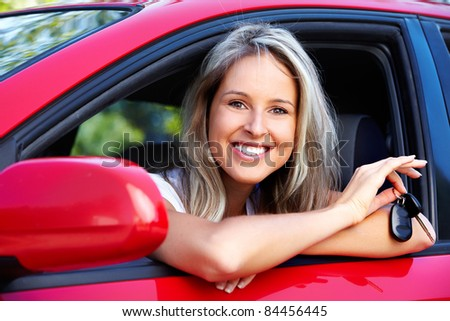 Happy smiling woman in a car. Driving.