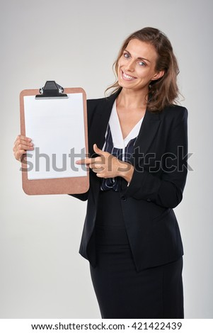Happy smiling woman in business suit pointing and promoting empty poster with copy space - stock photo