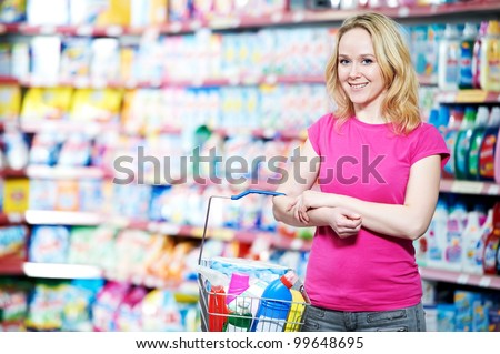 Happy smiling woman in front of household chemistry produces in shopping supermarket