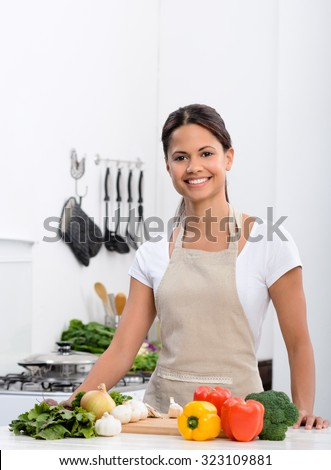 Happy smiling woman in kitchen with fresh produce vegetables preparing for a healthy meal