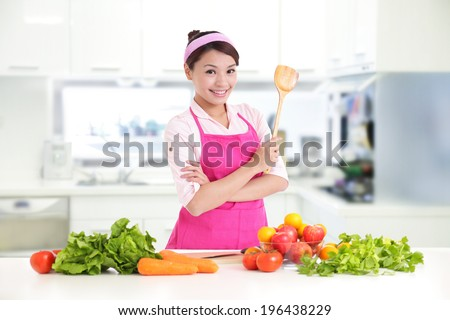 Happy smiling woman in kitchen with fresh produce vegetables preparing for a healthy meal, asian - stock photo