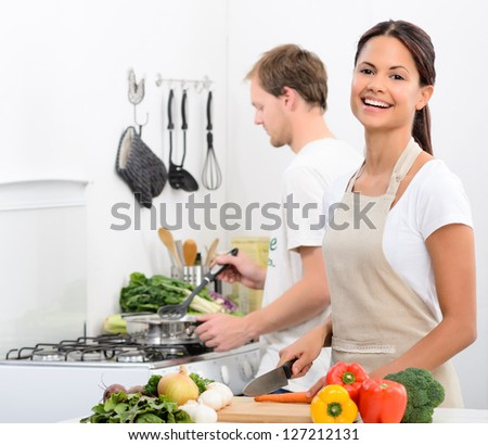 Happy smiling woman in kitchen with fresh produce vegetables preparing for a healthy meal, with partner husband cooking in background - stock photo