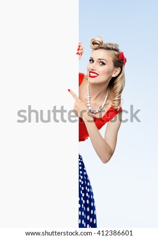 happy smiling woman in pin-up style dress, showing blank signboard with copyspace, on blue background. Caucasian blond model posing in retro fashion and vintage concept studio shoot. - stock photo