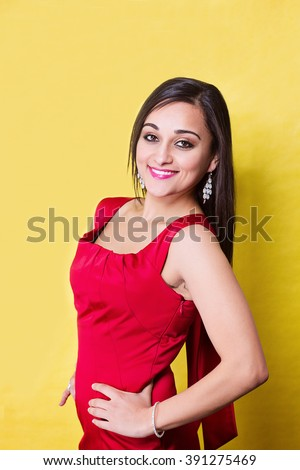 Happy smiling woman in red dress on yellow background