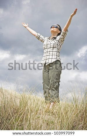 happy smiling woman in sand dunes holding arms to a stormy sky - stock photo