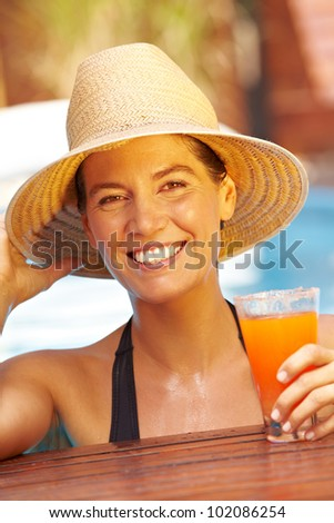 Happy smiling woman in summer with straw hat and cocktail in pool