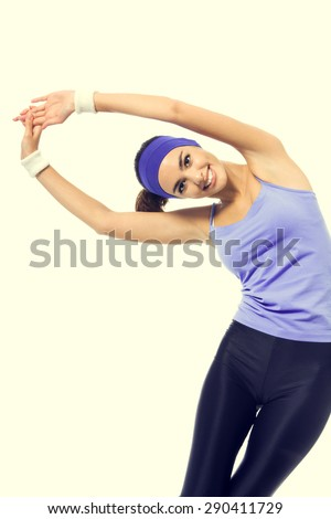 Happy smiling woman in violet sportswear doing stretching exercise or youga moves. Young sporty dark-haired model at studio shot. Health, beauty and fitness concept.