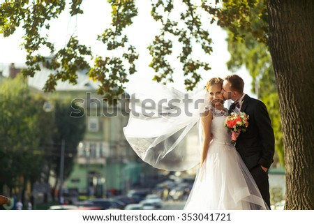 Happy smiling woman in wedding dress with long white veil and man kissing her. Stylish newlyweds under the tree.