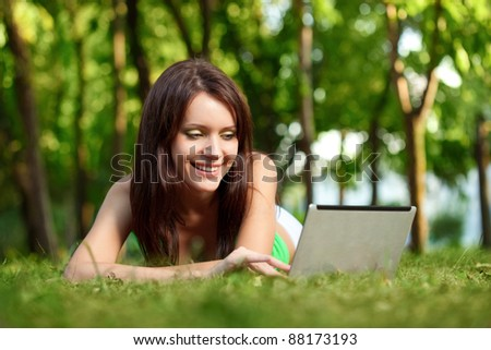 happy smiling woman laying on grass with laptop in summer park