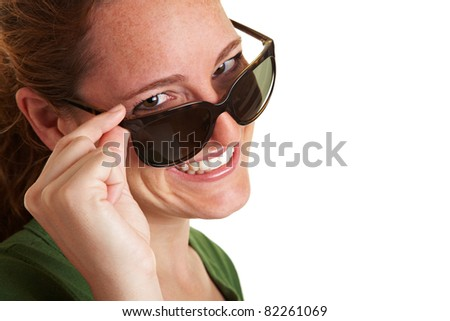 Happy smiling woman looking over the top of her sunglasses - stock photo