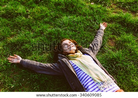 Happy smiling woman lying on grass in park with arms outstretched - stock photo