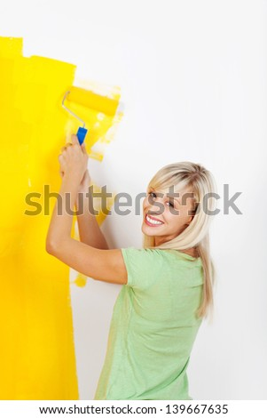 Happy smiling woman painting interior white wall in yellow color of new house - stock photo