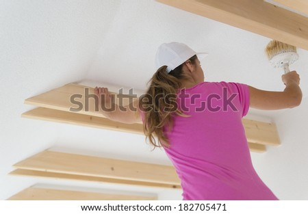Happy smiling woman painting the walls of new home with paintbrush