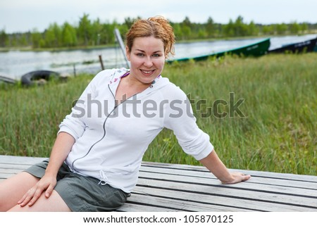 Happy smiling woman sitting on wooden boards on river edge. Copyspace