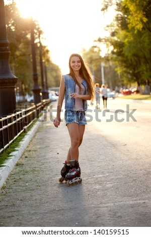 happy smiling woman skating outdoors  during sunset