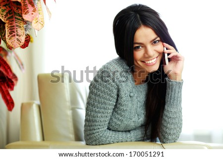 Happy smiling woman talking on the phone at home