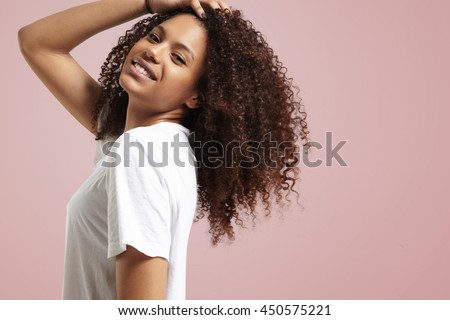 happy smiling woman touching her curly hair