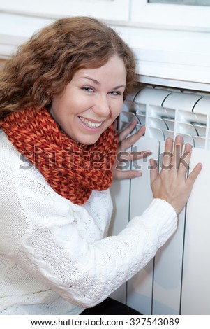 Happy smiling woman touching warm central heating convector - stock photo