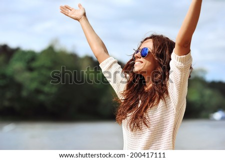 Happy smiling woman with hands raised - outdoor portrait  - stock photo
