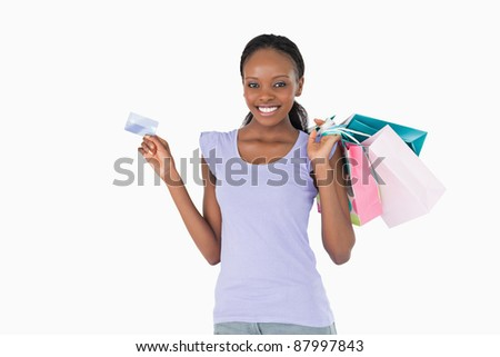 Happy smiling woman with her shopping and credit card on white background