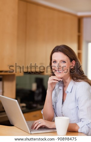 Happy smiling woman with laptop in the kitchen - stock photo