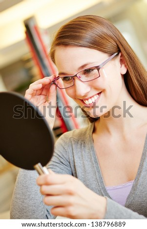 Happy smiling woman with new glasses looking in mirror at optician - stock photo