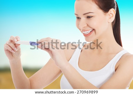 Happy smiling woman with pregnancy test.