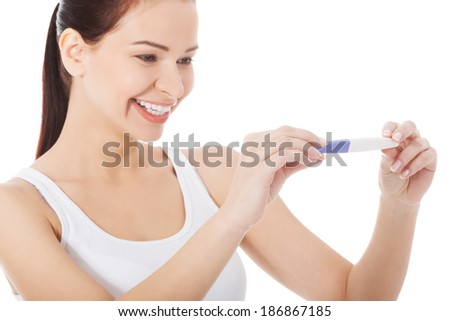 Happy smiling woman with pregnancy test. Isolated on white. - stock photo