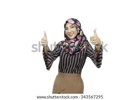 Happy smiling woman with thumbs up gesture, on white background. Beautiful smiling ordinary woman standing against white background. Thumb up. Gorgeous young brunette showing big thumbs up. Muslimah - stock photo
