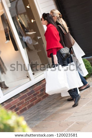 Happy smiling women shopping with white bags looking at the shop window - stock photo