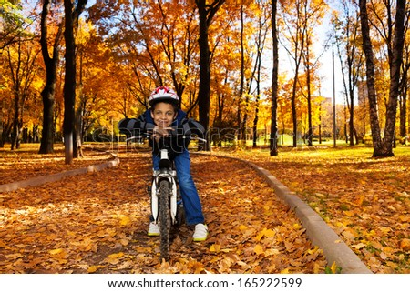 Happy smiling 8 years old black boy riding a bike in the autumn park leaning on bicycle stern