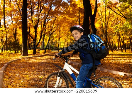 Happy smiling 8 years old black boy with backpack riding a bike in the autumn park full of orange leaves leaning on bicycle stern turning back - stock photo