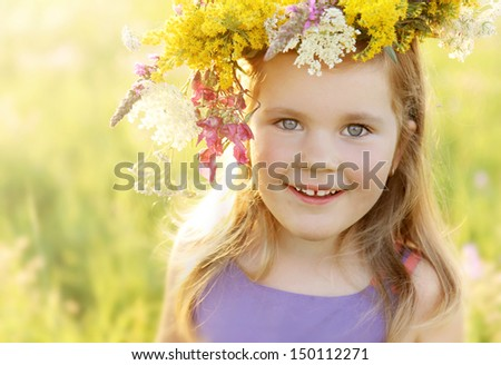 Happy smiling 3 years old girl in colorful wild flowers wreath on a sunny summer meadow field - stock photo