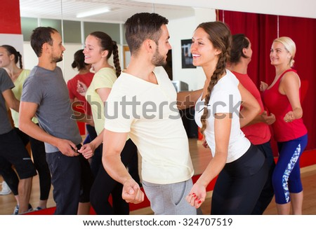 Happy smiling young adults having dance class at studio. Selective focus