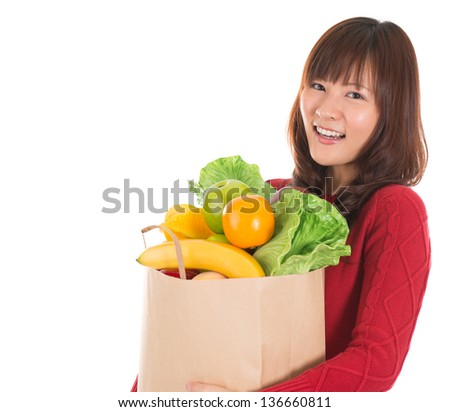 Happy smiling young Asian woman holding paper shopping bag full of groceries isolated on white - stock photo